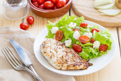Marinated Grilled Healthy Chicken Breast served with Fresh Salad on a Wooden Background royalty free stock photo