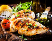 Marinated grilled healthy chicken breasts. Cooked on a summer BBQ and served with fresh herbs and lemon juice on a wooden board, close up view royalty free stock photos
