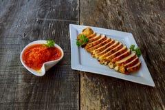 Marinated grillte die Hühnerbrüste, die mit frischen Kräutern auf einem hölzernen Brett gekocht wurden und gedient waren Lizenzfreie Stockfotos