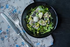 Marinated herring with arugula, onions, boiled quail eggs and lemon juice and olive oil. Delicious salad. Proper nutrition. Dark. Wooden background royalty free stock photography
