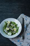 Marinated herring with arugula, onions, boiled quail eggs and lemon juice and olive oil. Delicious salad. Proper nutrition. Dark. Wooden background stock photos