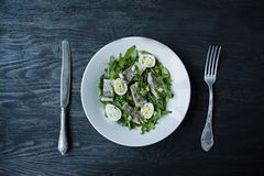 Marinated herring with arugula, onions, boiled quail eggs and lemon juice and olive oil. Delicious salad. Proper nutrition. Dark. Wooden background royalty free stock photos