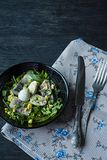 Marinated herring with arugula, onions, boiled quail eggs and lemon juice and olive oil. Delicious salad. Proper nutrition. Dark. Wooden background royalty free stock images