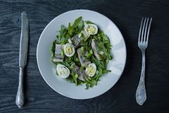 Marinated herring with arugula, onions, boiled quail eggs and lemon juice and olive oil. Delicious salad. Proper nutrition. Dark. Wooden background stock photo