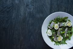 Marinated herring with arugula, onions, boiled quail eggs and lemon juice and olive oil. Delicious salad. Proper nutrition. Dark. Wooden background stock image