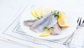 Marinated herring fillet on a white plate with lemon and onion. Traditional spring delicacy of the Netherlands. Typical cooking. Fish in Holland. Free space for stock photos
