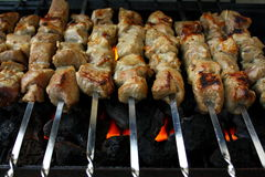 Marinated lamb meat grilling on metal skewer Stock Photos
