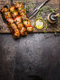 Marinated meat skewers with vegetables for grill or BBQ , fresh seasoning nad oil on dark rustic wooden background, top view. Place for text, border, vertical royalty free stock image