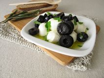 Marinated mozzarella with black olives, olive oil and mustard leaves Royalty Free Stock Image