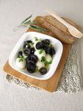 Marinated mozzarella with black olives, olive oil and mustard leaves Stock Photo
