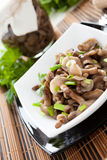 Marinated mushrooms and green onions in a white bowl and a glass Royalty Free Stock Images