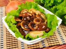 Marinated mushrooms with lettuce leaves. On a napkin from a bamboo Royalty Free Stock Images