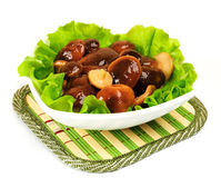 Marinated mushrooms with lettuce leaves. On a white background Royalty Free Stock Images