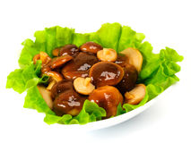Marinated mushrooms with lettuce leaves. On a white background Royalty Free Stock Photography