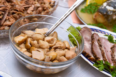Marinated mushrooms (porcini). Party food, a bowl of pickled porcini mushrooms set on a table Royalty Free Stock Photo