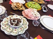 Marinated mushrooms, stuffed eggs, rolls of ham, stuffed chicken- holiday family dinner Stock Photos