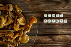 Marinated mushrooms in a transparent plate on a wooden table. Letters with the name of the dish stock images