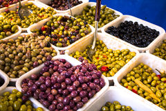 Marinated olives. Multicolored olives in plastic tubs exposed in the market for tasting and sale Royalty Free Stock Photo