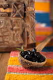 Marinated Olives in old spoon with moroccan  ornament on wood Stock Photography