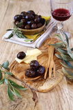 Marinated olives, slices of cheese and wineglass Royalty Free Stock Photography