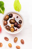 Marinated Olives on white wooden background Royalty Free Stock Image