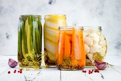 Marinated pickles variety preserving jars. Homemade green beans, squash, carrots, cauliflower pickles. Fermented food.  Royalty Free Stock Images