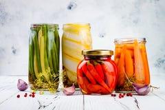 Marinated pickles variety preserving jars. Homemade green beans, squash, radish, carrots, cauliflower pickles. Fermented food royalty free stock photo