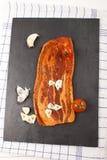 Marinated pork bacon with garlic on slate Stock Image