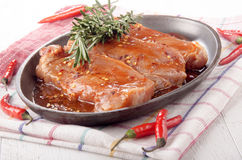 Marinated pork chops in a pan Royalty Free Stock Images