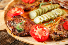 Marinated pork grilled. Spiced pork chops barbecue on a wooden board with tomatoes and pickles Stock Images