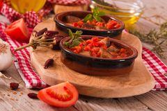 Marinated pork loin in tomato sauce. Marinated pork loin in tomato sauce on cutting board stock images
