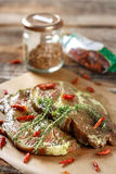 Marinated pork neck and condiments. Seasoned pork neck ready for barbecue on a wooden board Stock Images