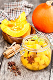 Marinated pumpkin dices in a glass container on a wooden table. Stock Images