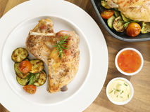 Marinated rabbit and grilled vegetable - tomatoes and zucchini. Top view. Portion of marinated roasted rabbit served with grilled vegetable - tomatoes and Stock Photography