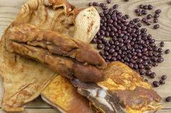 Marinated rack, ear, foot of pig and red edible bean over wood. Royalty Free Stock Photo