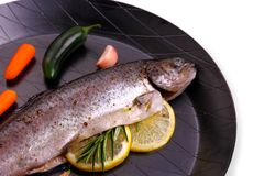 Marinated rainbow trout with lemon, carrot on frying pan. Close up stock photo