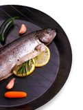 Marinated rainbow trout with lemon, garlic on frying pan. Top view stock photography