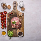 Marinated raw beef with herbs and tomatoes on a branch and spices on a cutting board on wooden rustic background top view border, Royalty Free Stock Photography