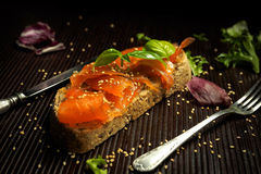 Marinated salmon with basil and sesame seeds on slice of bread Stock Photography