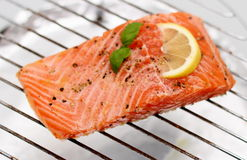 Marinated salmon fillet with lemon on grill Royalty Free Stock Photos