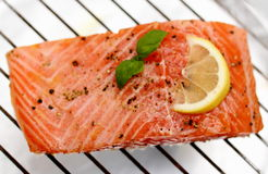 Marinated salmon fillet with lemon on grill Stock Photography