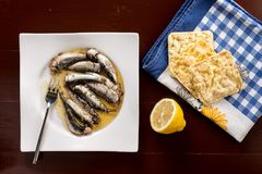 Marinated sardines in the oil served with lemon and corn bread Royalty Free Stock Images