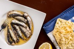 Marinated sardines in the oil served with lemon and corn bread Royalty Free Stock Image