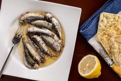 Marinated sardines in the oil served with lemon and corn bread Stock Photo