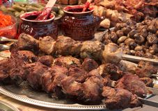 Marinated shashlik preparing on a barbecue grill over charcoal. Royalty Free Stock Images