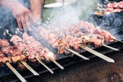 Marinated shashlik preparing on a barbecue grill over charcoal. Roasted stacked meat Shish kebab popular Eastern Europe. Shashlyk. Skewered meat originally made Royalty Free Stock Photo