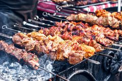 Marinated shashlik preparing on a barbecue grill over charcoal. Shashlik or Shish kebab popular in Eastern Europe. Royalty Free Stock Photos