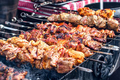 Marinated shashlik preparing on a barbecue grill over charcoal. Shashlik or Shish kebab popular in Eastern Europe. Stock Photography