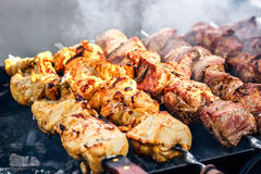 Marinated shashlik preparing on a barbecue grill over charcoal. Shashlik or Shish kebab popular in Eastern Europe. Royalty Free Stock Photo