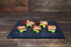 Marinated shrimps on grilled zucchinis with white sauce Stock Photos